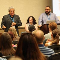 Three people stand or sit at the front of a room filled with people and talk to them at a conference.