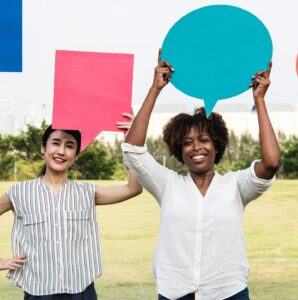 Several women in button-down shirts stand outside and hold colorful speech bubble cut outs over their heads.
