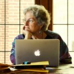 A woman with short, gray hair has her face resting on her hand as she sits at her computer.