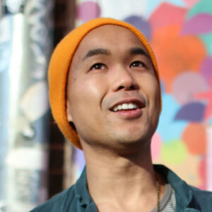 An Asian American man with a bright, orange cap stands in front of a colorful backdrop and smiles as he looks up.