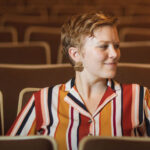 Hannah has a colorful, striped shirt on and short, cropped blonde hair. She sits in an auditorium.